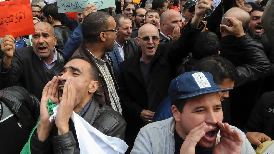 Teachers, health workers and local civil servants shout as part of a a three-day strike over plans to tighten spending and increase the retirement age as part of the 2017 finance bill, Monday Nov. 21, 2016 in Algiers. The government, coping with a fall in oil revenue, wants to raise taxes, freeze some salaries and set a minimum retirement age of 60. (AP Photo/Sidali Djarboub)