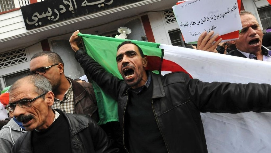 Teachers, health workers and local civil servants, one holding an Algerian flag, shout as part of a a three-day strike over plans to tighten spending and increase the retirement age as part of the 2017 finance bill, Monday Nov. 21, 2016 in Algiers. The government, coping with a fall in oil revenue, wants to raise taxes, freeze some salaries and set a minimum retirement age of 60. (AP Photo/Sidali Djarboub)