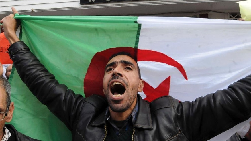 A union member holding an Algerian flag, shout as part of a a three-day strike over plans to tighten spending and increase the retirement age as part of the 2017 finance bill, Monday Nov. 21, 2016 in Algiers. The government, coping with a fall in oil revenue, wants to raise taxes, freeze some salaries and set a minimum retirement age of 60. (AP Photo/Sidali Djarboub)