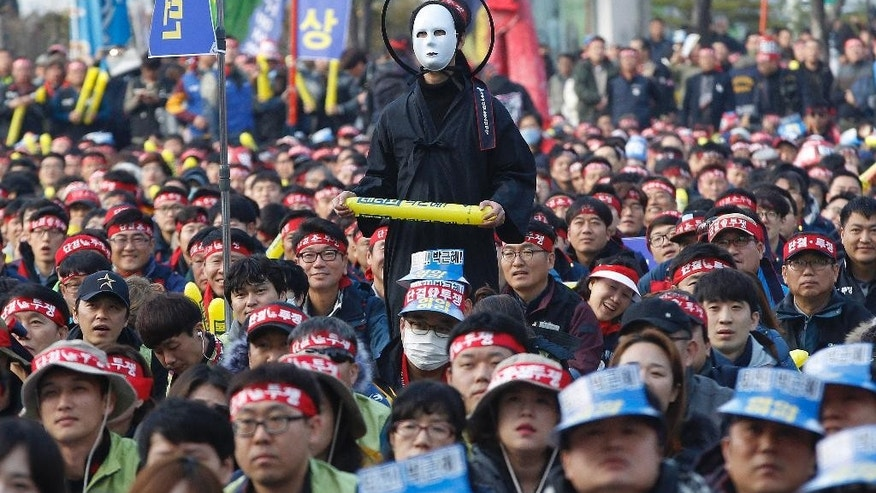 In this Saturday, Nov. 19, 2016 photo, a South Korean protester wearing a mask listens to a speech during a rally calling for South Korean President Park Geun-hye to step down in Seoul, South Korea. For the fourth straight weekend, masses of South Koreans were expected to descend on major avenues in downtown Seoul demanding an end to the presidency of Park, who prosecutors plan to question soon over an explosive political scandal. (AP Photo/Ahn Young-joon, File)