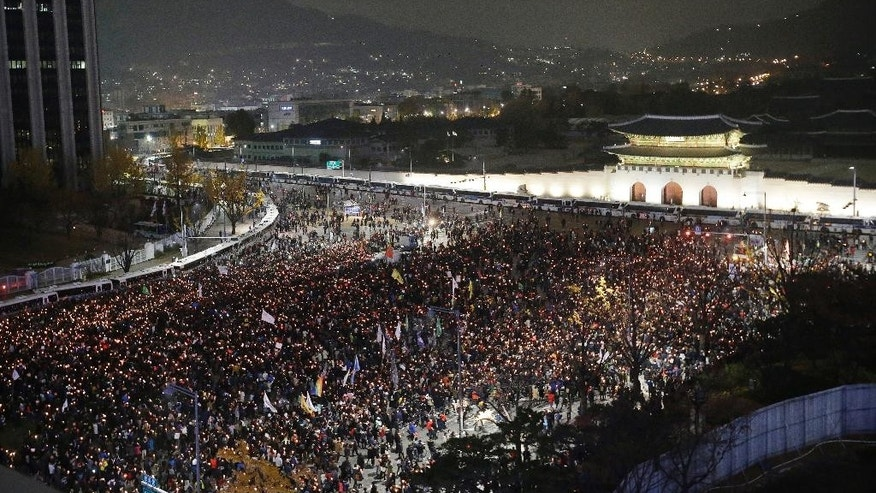FILE - In this Saturday, Nov. 19, 2016, file photo, South Korean protesters march in front of Gwanghwamun, the main gate to the royal Gyeongbokgung Palace of the Joseon dynasty, on their way to the presidential Blue House during a rally calling for South Korean President Park Geun-hye to step down in Seoul. A scandal that has captivated a nation took a new twist this weekend when prosecutors directly linked South Korea's president to alleged misdeeds by a shadowy confidante seen as pulling government strings.With hundreds of thousands taking to the streets each weekend in anger, President Park Geun-hye is digging in her heels, refusing to meet with prosecutors. The looming question now is: Will legislators take the politically risky path of impeaching her? (AP Photo/Ahn Young-joon, File)