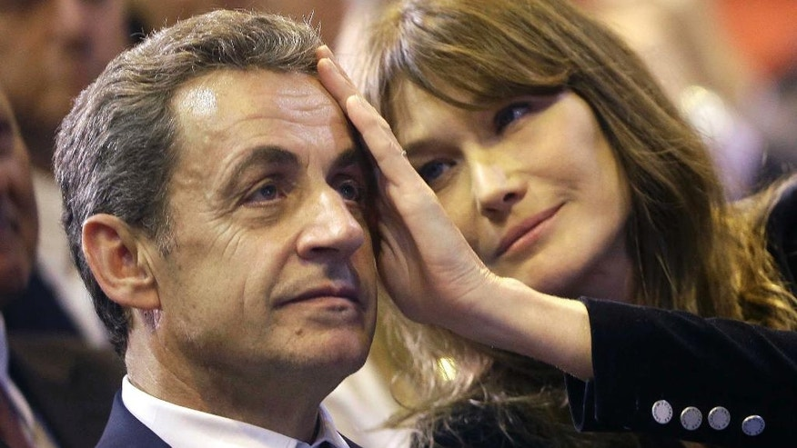 FILE - In this Thursday, Oct. 27, 2016 file picture, Carla Bruni-Sarkozy caresses the brow of her husband, the former French President and candidate for France's conservative presidential primary, Nicolas Sarkozy, during a campaign meeting in Marseille, southern France. (AP Photo/Claude Paris, File)