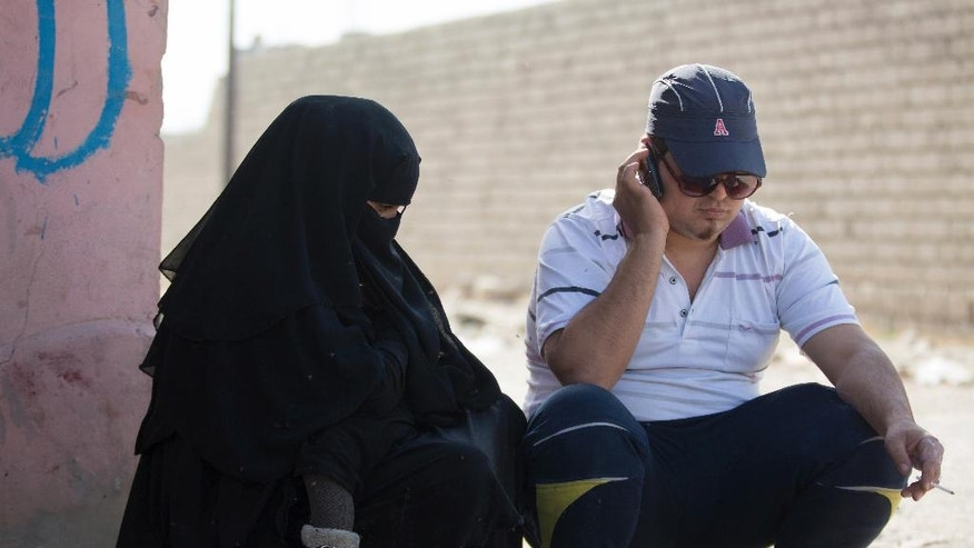 In this Sunday, Nov. 12, 2016 photo, a man who identified himself as Omar Danoun talks on the phone during an interview with The Associated press in Gogjali, Iraq. Danoun was taken into custody later in the interview by Iraqi soldiers who overheard and said he seemed to have a Syrian Accent, and who believed he was an Islamic Stage group member. (AP Photo/NishNalbandian)