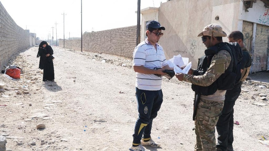 A man who identified himself as Omar Danoun, who claimed to be from Mosul, has his papers checked and is taken into custody by Iraqi soldiers at a collection point for displaced Iraqis in Gogjali, Iraq, Nov. 12, 2016. The soldiers overheard his interview with The Associated Press and became suspicious of his accent, believing he was Syrian and a member of the Islamic State group. (AP Photo/Nish Nalbandian)