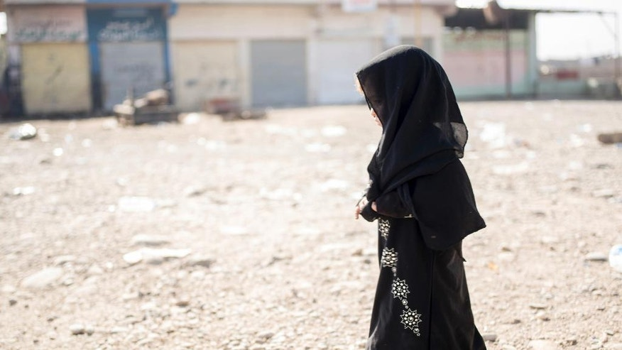 In this Sunday, Nov. 12, 2016 photo, the daughter of a man a man who identified himself as Omar Danoun walks into a collection point for people displaced by fighting in Mosul, in Gogjali, Iraq. Danoun, who was taken into custody by Iraqi soldiers during his interview with The Associated Press, claimed he was from Mosul. The soldiers believed he was with the Islamic State group and that he seemed to speak with a Syrian accent instead of an Iraqi accent. (AP Photo/Nish Nalbandian)