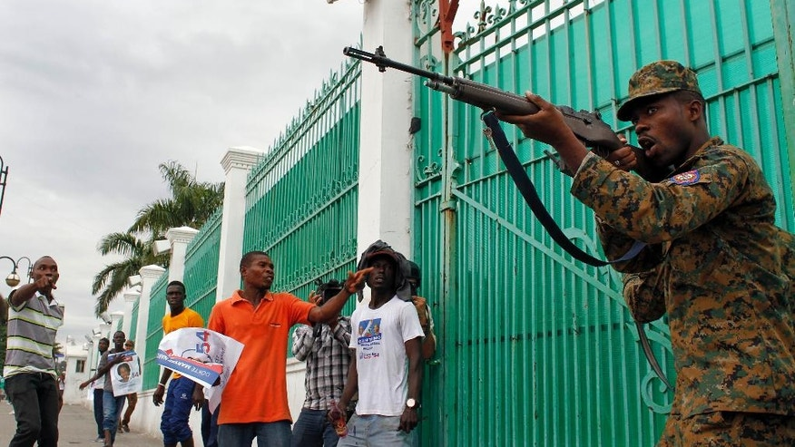 A police officer points his rifle at supporters of presidential candidate Maryse Narcisse from Fanmi Lavalas political party during a protest in Port-au-Prince, Haiti, Monday, Nov. 21, 2016. During Haiti's repeatedly derailed presidential election there were 43 arrests for various charges such as illegal gun possession and assault. Hours after voting ended, a major fire raged at a central market in the hillside Petionville district above Port-au-Prince but the cause wasn't immediately clear.(AP Photo/Ricardo Arduengo)