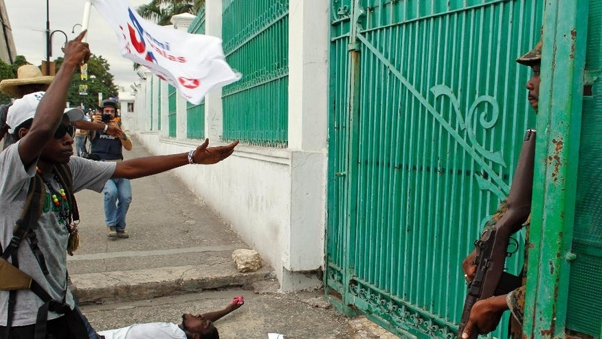 A man plays dead in front of a police officer after he fired three warning shots in the air during a protest of supporters of presidential candidate Maryse Narcisse from Fanmi Lavalas political party in Port-au-Prince, Haiti, Monday, Nov. 21, 2016. During Haiti's repeatedly derailed presidential election there were 43 arrests for various charges such as illegal gun possession and assault. Hours after voting ended, a major fire raged at a central market in the hillside Petionville district above Port-au-Prince but the cause wasn't immediately clear. (AP Photo/Ricardo Arduengo)