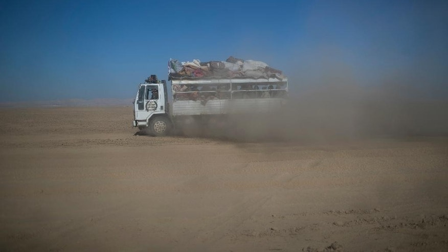 A truck carrying Popular Mobilization Units fighters rides through the desert on their way to fight against Islamic State militants in the airport of Tal Afar, west of Mosul, Iraq, Sunday, Nov. 20, 2016.  Iraqi troops on Sunday fortified their positions in Mosul neighborhoods retaken from the Islamic State group as their advance toward the city center was slowed by sniper fire and suicide bombings, as well as concern over the safety of civilians. (AP Photo/Felipe Dana)