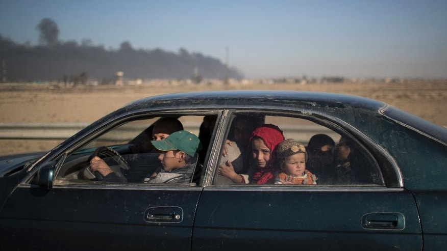 An Iraqi family sits inside a car as they wait at a checkpoint near Qayara, south of Mosul, Iraq, Sunday, Nov. 20, 2016. Iraqi troops on Sunday fortified their positions in Mosul neighborhoods retaken from the Islamic State group as their advance toward the city center was slowed by sniper fire and suicide bombings, as well as concern over the safety of civilians. (AP Photo/Felipe Dana)
