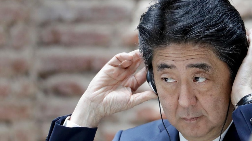 Japan's Prime Minister Shinzo Abe puts headphone on during an event at the government house in Buenos Aires, Argentina, Monday, Nov. 21, 2016. Abe is on an official visit to Argentina after attending the Asia-Pacific Economic Cooperation summit in Peru. (AP Photo/Natacha Pisarenko)