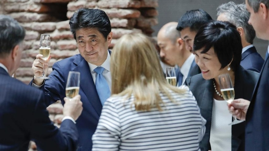 Japan's Prime Minister Shinzo Abe, left, toasts during a lunch at the government house in Buenos Aires, Argentina, Monday, Nov. 21, 2016. Abe is on an official visit to Argentina after attending the Asia-Pacific Economic Cooperation summit in Peru. (AP Photo/Natacha Pisarenko)
