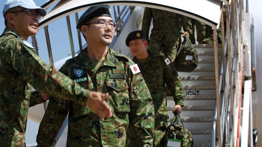 Squad leader Captain Yoshino Tanaka, center-left, and other members of Japan Self-Defense Forces arrive as part of a first batch who have a broader mandate to use force, at the airport in Juba, South Sudan Monday, Nov. 21, 2016. Japanese peacekeepers, with a broader mandate to use force, landed in South Sudan in the first such deployment of the country's troops overseas with those expanded powers in nearly 70 years. (AP Photo/Justin Lynch)