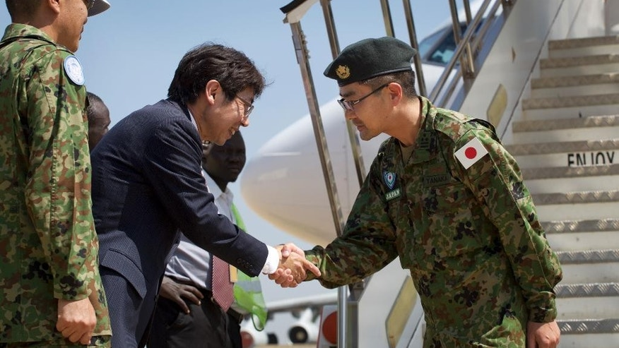 Squad leader Captain Yoshino Tanaka, right, is greeted by Japan's ambassador to South Sudan Kiya Masahiko, 2nd left, as he and other members of Japan Self-Defense Forces arrive as part of a first batch who have a broader mandate to use force, at the airport in Juba, South Sudan Monday, Nov. 21, 2016. Japanese peacekeepers, with a broader mandate to use force, landed in South Sudan in the first such deployment of the country's troops overseas with those expanded powers in nearly 70 years. (AP Photo/Justin Lynch)