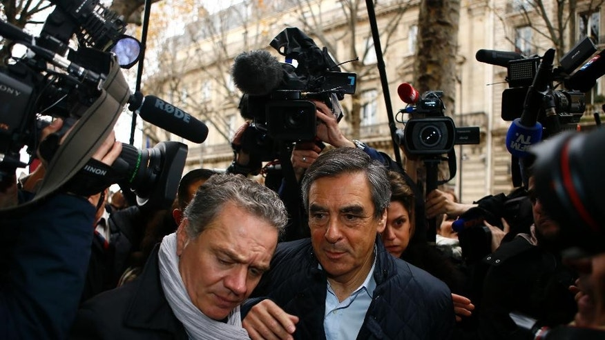 Francois Fillon, right, arrives with his bodyguard at his campaign headquarters in Paris, Monday, Nov.21, 2016. Former Prime Ministers Fillon and Alain Juppe will meet in a runoff next Sunday for the nomination to be France's conservative candidate for president. (AP Photo/Francois Mori)