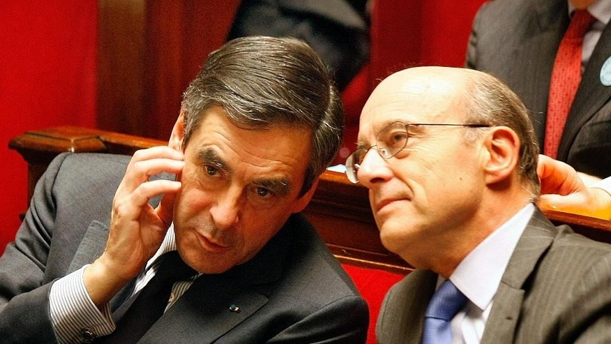 FILE - In this March 22, 2011 file photo, then French Prime Minister Francois Fillon, left, speaks with then Foreign Minister Alain Juppe, at the National Assembly in Paris. Fillon and Juppe will meet in a runoff next Sunday for the nomination to be France's conservative candidate for president. (AP Photo/Remy de la Mauviniere, File)