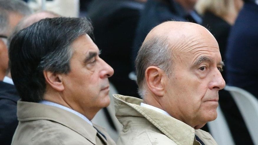 FILE - In this Sept.19, 2016 former French Prime Ministers Francois Fillon, left, and Alain Juppe attend a ceremony for victims of terrorism in Paris. The two ex-prime ministers will meet in a runoff next Sunday for the nomination to be France's conservative candidate for president. (AP Photo/Michel Euler, Pool, File)
