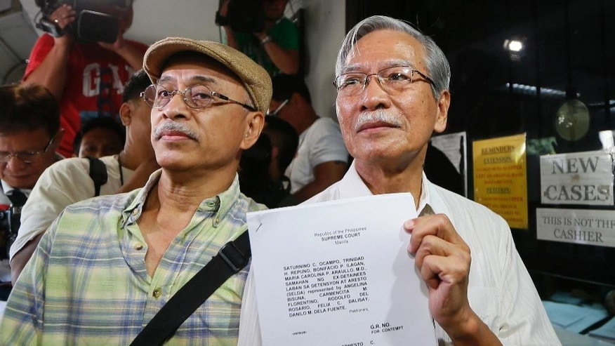 Activists Saturnino Ocampo, right, and Bonifacio Ilagan hold documents after filing a petition at the Supreme Court seeking to cite the Marcos' heirs and officials in contempt for carrying out the burial even before the highest court's ruling allowing it became final and executory Monday, Nov. 21, 2016 in Manila, Philippines. The late Philippine dictator Ferdinand Marcos was buried in a secrecy-shrouded ceremony at the Heroes' Cemetery Friday, Nov. 18, 2016. (AP Photo/Bullit Marquez)