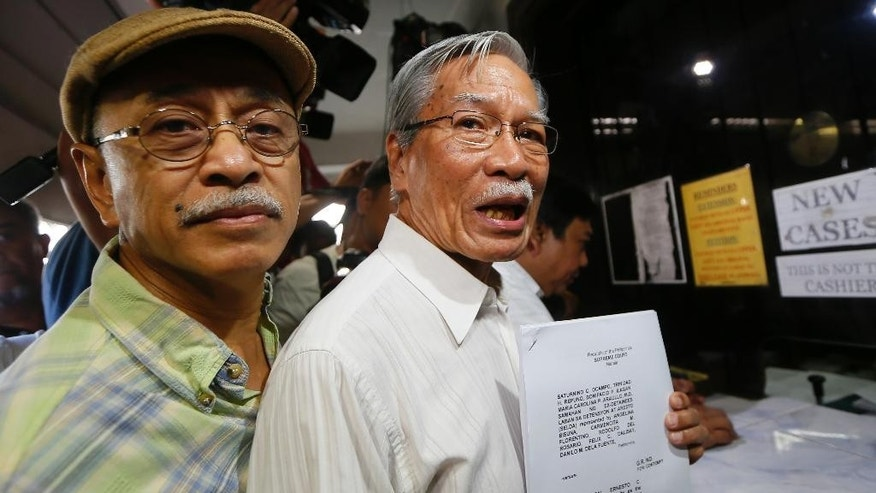 Activists Saturnino Ocampo, right, and Bonifacio Ilagan hold documents after filing a petition at the Supreme Court seeking to hold the Marcos' heirs and officials in contempt for carrying out the burial even before the highest court had heard final appeals against it Monday, Nov. 21, 2016 in Manila, Philippines. The late Philippine dictator Ferdinand Marcos was buried in a secrecy-shrouded ceremony at the Heroes' Cemetery Friday, Nov. 18, 2016. (AP Photo/Bullit Marquez)
