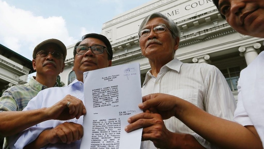 Activists, from left, Bonifacio Ilagan, Neri Colmenares, Saturnino Ocampo, and attorney Ephraim Cortez hold documents after filing a petition at the Supreme Court seeking to hold the Marcos' heirs and officials in contempt for carrying out the burial even before the highest court had heard final appeals against it Monday, Nov. 21, 2016 in Manila, Philippines. The late Philippine dictator Ferdinand Marcos was buried in a secrecy-shrouded ceremony at the Heroes' Cemetery Friday, Nov. 18, 2016. (AP Photo/Bullit Marquez)