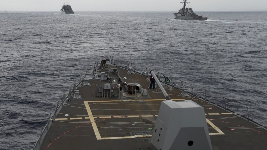 FILE - This Oct. 17, 2016 file image provided by the U.S. Navy,  shows the guided missile destroyer USS Decatur, right, pulling into position behind the Military Sealift Command USNS Matthew Perry, during a replenishment-at-sea, seen from the bridge of the guided-missile destroyer USS Spruance, in the South China Sea. The commander of U.S. forces in the Pacific Adm. Harry Harris said he's concerned with China's assertiveness in the South China Sea and the East China Sea as he headed to the Philippines to discuss the next round of joint exercises. (U.S. Navy/Petty Officer 2nd Class Will Gaskill via AP, File)