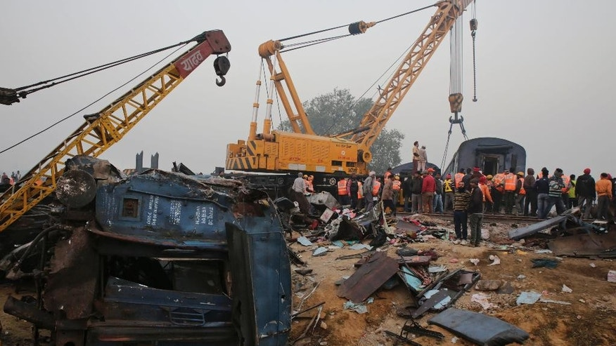 Rescuers work at the site after 14 coaches of an overnight passenger train rolled off the track near Pukhrayan village in Kanpur Dehat district of the northern Indian state of Uttar Pradesh, India, Monday, Nov. 21, 2016. Scores of passengers died and scores more were injured in the accident. (AP Photo/Rajesh Kumar Singh)