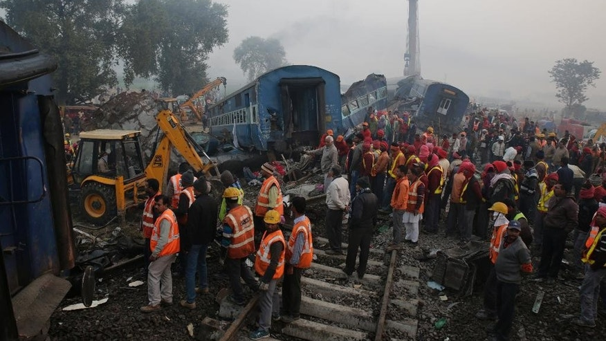 Rescuers work at the site after 14 coaches of an overnight passenger train rolled off the track near Pukhrayan village in Kanpur Dehat district of the northern Indian state of Uttar Pradesh, India, Monday, Nov. 21, 2016. Dozens died and dozens more were injured in the accident. (AP Photo/Rajesh Kumar Singh)