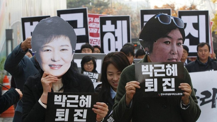 "FILE - In this Nov. 18, 2016, file photo, protesters wearing masks of South Korean President Park Geun-hye, left and Choi Soon-sil, Park's longtime friend, in Seoul, South Korea. South Korean prosecutors on Sunday, Nov. 20, 2016, said they believe Park conspired in criminal activities of a secretive confidante who allegedly manipulated government affairs and exploited her presidential ties to amass an illicit fortune - a damning revelation that may convince opposition parties to push for her impeachment. The placards held by the protesters read: ""Park Geun-hye should step down."" (AP Photo/Ahn Young-joon, File)"