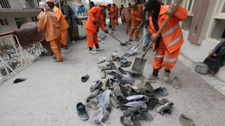 Nov. 21, 2016: Afghan Municipality workers collect shoes of victims in front the Baqir-ul Ulom mosque after a suicide attack, in Kabul, Afghanistan.