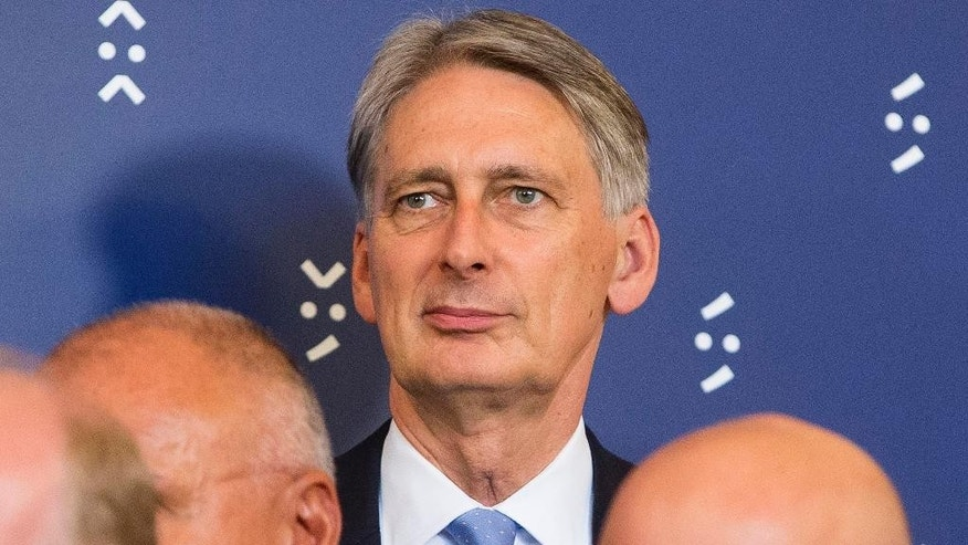 FILE - In this Friday, Sept. 9, 2016 file photo, British Minister of Finance Philip Hammond prepares for a group photo, after the Eurogroup's deliberations at the Informal Meeting of Ministers for economic and financial affairs, in Bratislava, Slovakia. Britain's Treasury chief Philip Hammond said Sunday Nov. 20, 2016, the economy could face a slowdown because of the uncertainty caused by the U.K.'s decision to leave the European Union.  (AP Photo/Bundas Engler, File)