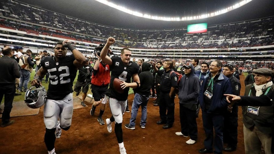 Oakland Raiders quarterback Derek Carr, center, reacts with teammate defensive end Khalil Mack (52) after an NFL football game against the Houston Texans Monday, Nov. 21, 2016, in Mexico City. The Raiders won, 27-20. (AP Photo/Eduardo Verdugo)