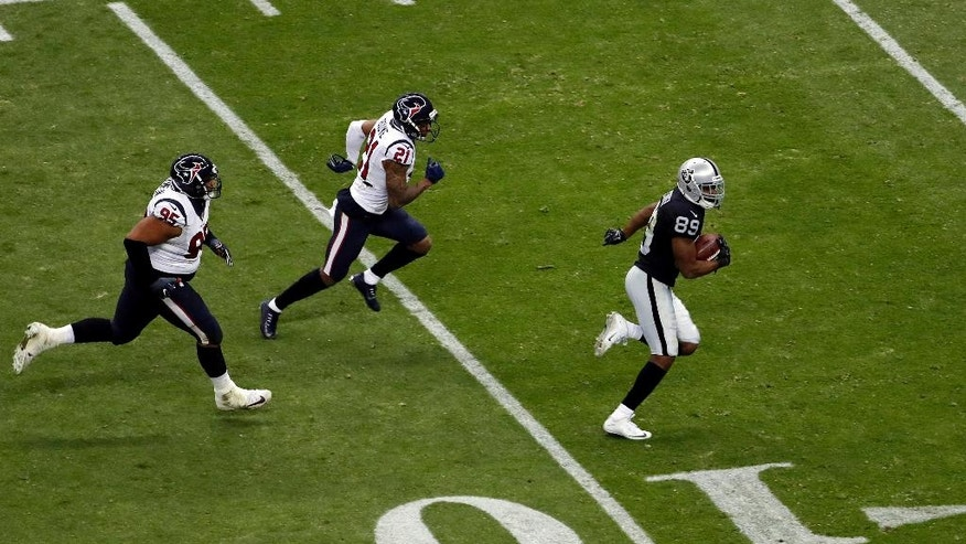 Oakland Raiders wide receiver Amari Cooper, right, gets away from Houston Texans cornerback A.J. Bouye (21) and defensive end Christian Covington (95) on his way to scoring a touchdown during the second half of an NFL football game Monday, Nov. 21, 2016, in Mexico City. (AP Photo/Dario Lopez-Mills)
