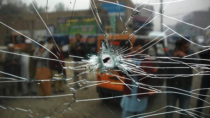 Pakistani cameramen film a shattered windshield of a vehicle of paramilitary troops at the site bomb blast in Peshawar, Pakistan, Tuesday, Nov. 22, 2016. A Pakistani police official says a bomb blast has killed some paramilitary officers in the northwestern city of Peshawar. Wajid Khan says the bomb, which was apparently detonated by remote control, exploded when a patrol of paramilitary police was passing by. (AP Photo/Muhammad Sajjad)