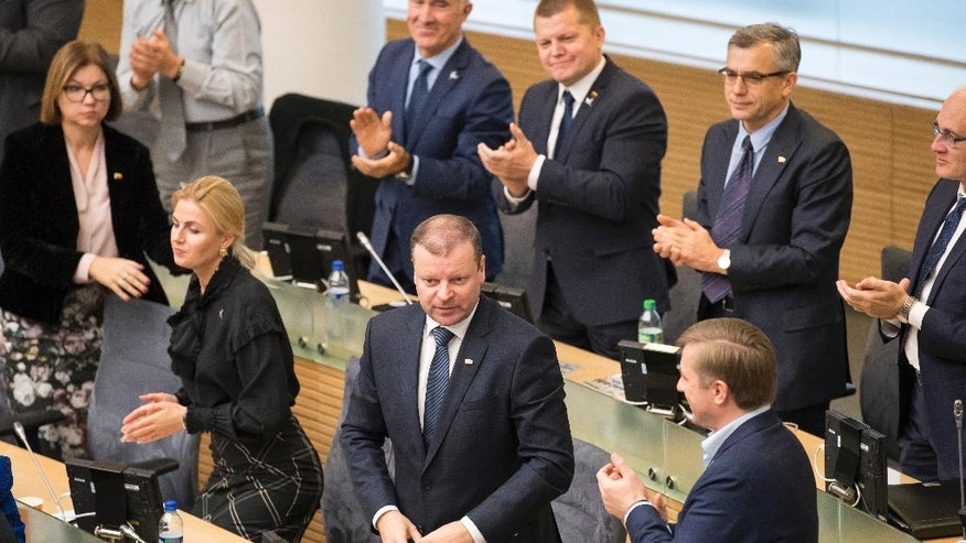 Members of Lithuania's parliament applaud Lithuania's Peasant and Green's Union (LPGU) party leader Salius Skvernelis in Vilnius, Lithuania, Tuesday, Nov. 22, 2016. Lithuania's parliament approved Skvernelis as the new prime minister on Tuesday. (AP Photo/Mindaugas Kulbis)