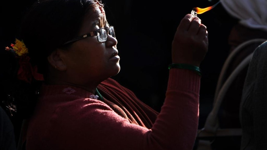 A devotee lights oil lamp while she offer prayers at the Boudhanath Stupa that was Tuesday opened to the public after restoration in Kathmandu, Nepal, Tuesday, Nov. 22, 2016. A year and a half after a colossal earthquake destroyed hundreds of its treasured historic sites, Nepal celebrated the restoration of the iconic Buddhist monument topped in gold that towers above Kathmandu. (AP Photo/Niranjan Shrestha)