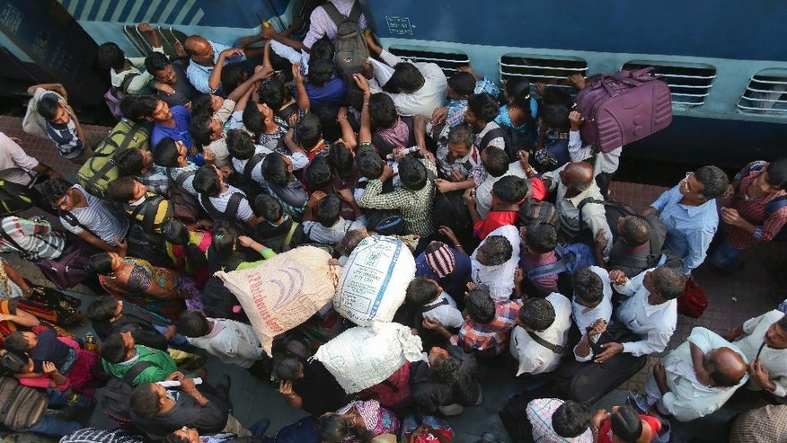 FILE- In this Jan. 13, 2016 file photo, Indians scramble to enter a train in Hyderabad, India. It's often described as India's lifeline, transporting 23 million people across this vast South Asian country each day. For more than 150 years, India's sprawling rail network has helped knit this disparate country together. For years, it's been clear that the much-romanticized legacy of British colonial rule, built more than 160 years ago, is badly hobbled by funding shortfalls, aging tracks, outdated signaling and communications systems and a volume of traffic that has pushed these systems beyond their limits. (AP Photo/Mahesh Kumar A, File)