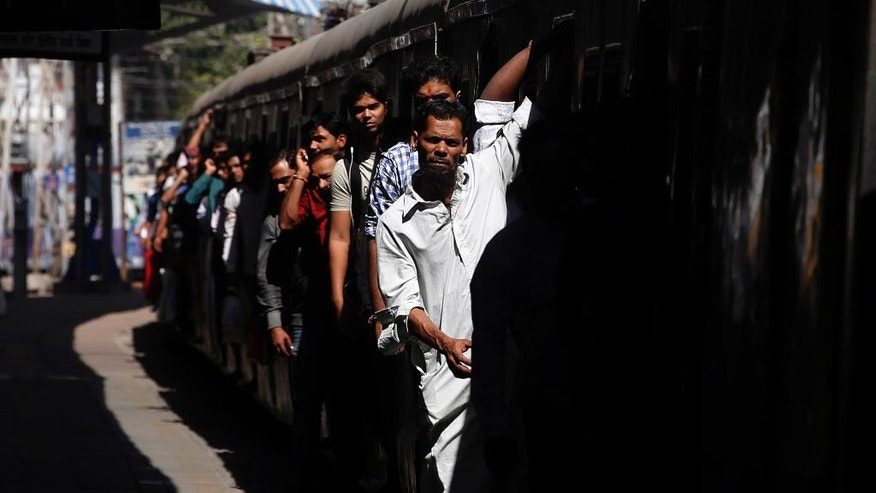 FILE- In this Jan. 22, 2016 file photo, commuters hang out of an overcrowded suburban train as it arrives in Mumbai Central Train Station in Mumbai, India. India's sprawling rail network, the world's third largest, operates more than 12,600 trains carrying passengers and cargo across 115,000 kilometers (71,000 miles) of track. But not all is well with the Indian Railways. For years, it's been clear that the much-romanticized legacy of British colonial rule, built more than 160 years ago, is badly hobbled by funding shortfalls, aging tracks, outdated signaling and communications systems and a volume of traffic that has pushed these systems beyond their limits. (AP Photo/Rajanish Kakade, File)