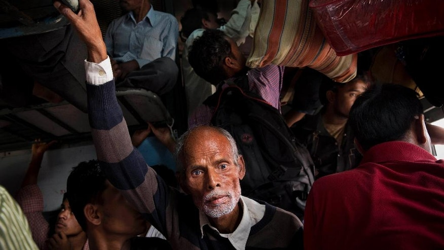 FILE- In this Oct. 28, 2014 file photo, Indian passengers jostle for space inside a train coach, crowded with people trying to reach their homes ahead of Hindu festival Chhath Puja at a railway station in New Delhi. India's sprawling rail network, the world's third largest, operates more than 12,600 trains carrying passengers and cargo across 115,000 kilometers (71,000 miles) of track. But not all is well with the Indian Railways. For years, it's been clear that the much-romanticized legacy of British colonial rule, built more than 160 years ago, is badly hobbled by funding shortfalls, aging tracks, outdated signaling and communications systems and a volume of traffic that has pushed these systems beyond their limits. (AP Photo/Bernat Armangue, File)