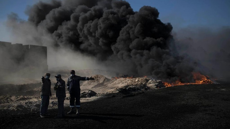Oil workers try to extinguish burning oil fields in Qayara, south of Mosul, Iraq, Tuesday, Nov. 22, 2016. For months, residents of the Iraqi town of Qayara have lived in darkness from a cloud of toxic fumes released by oil fields lit by retreating Islamic State fighters. (AP Photo/Felipe Dana)