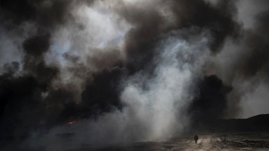 An oil worker walks next to burning oil fields in Qayara, south of Mosul, Iraq, Tuesday, Nov. 22, 2016. For months, residents of the Iraqi town of Qayara have lived in the darkness from a cloud of toxic fumes released by oil fields lit by retreating Islamic State fighters. (AP Photo/Felipe Dana)