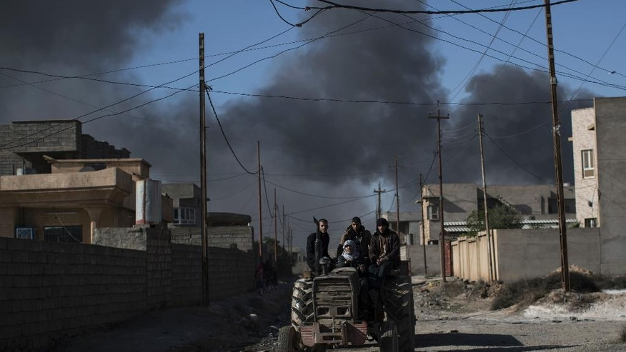 People ride on a tractor in Qayara, south of Mosul, Iraq, Tuesday, Nov. 22, 2016. For months, residents of the Iraqi town of Qayara have lived in darkness from a cloud of toxic fumes released by oil fields lit by retreating Islamic State fighters. (AP Photo/Felipe Dana)