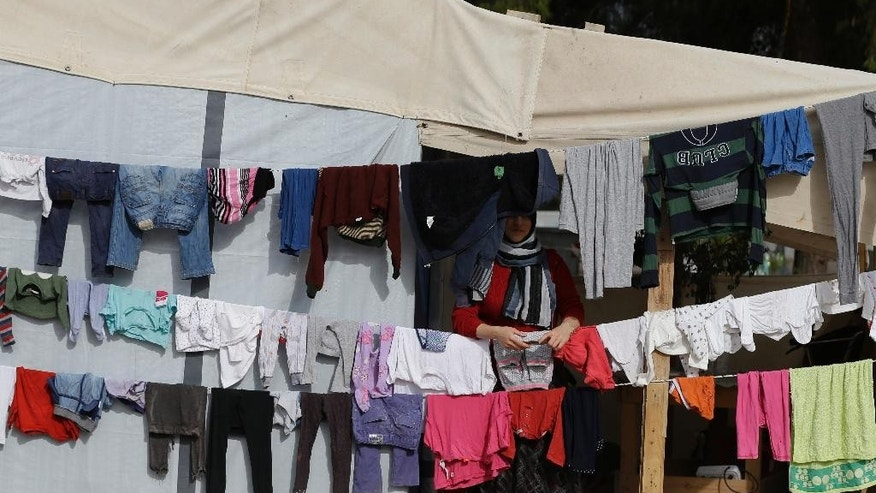 A woman stands behind her laundry at the refugee camp of Ritsona about 86 kilometers (53 miles) north of Athens, on Tuesday, Nov. 22, 2016. Around 680 people are staying in new container houses as over 62,000 refugees and migrants are stranded in Greece after a series of Balkan border closures. (AP Photo/Thanassis Stavrakis)