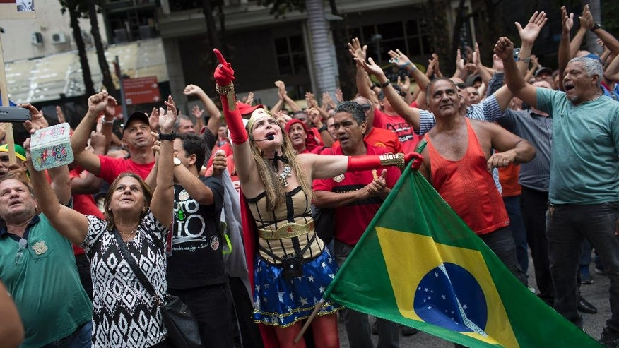 Demonstrators, one dressed in a Wonder Woman costume, shout outside the state of Rio de Janeiro's legislative assembly building where lawmakers are discussing austerity measures in Rio de Janeiro, Brazil, Tuesday, Nov. 22, 2016. State legislators are struggling to agree on a plan to deal with a deepening financial crisis and two former Rio governors have been arrested this week in connection with corruption and vote-buying allegations. (AP Photo/Leo Correa)