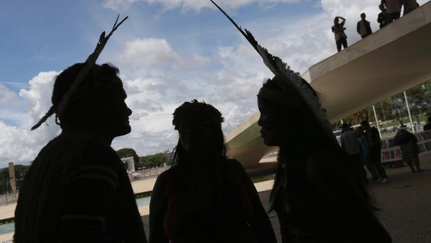 Indigenous people block the main entrance of Planalto presidential palace, where security officers stand above, top right, as a form of protest in Brasilia, Brazil, Tuesday, Nov. 22, 2016. Brazil's various indigenous groups are demanding the government recognize their ancestral lands and provide group land titles. (AP Photo/Eraldo Peres)