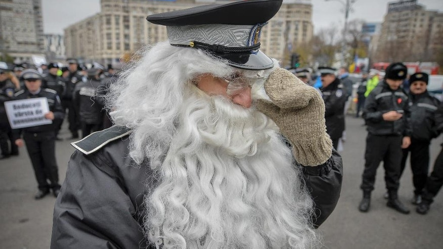 A Romanian policeman wears a false beard and glasses covered in tape to suggest old age and blurred vision during a protest demanding the lowering of the retirement age for police officers in Bucharest, Romania, Wednesday, Nov. 22, 2016. The protest was joined by more than one thousand officers asking the government to lower retirement age which is currently 65 years-old. (AP Photo/Andreea Alexandru)