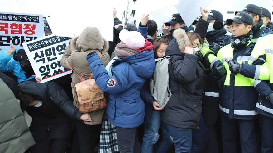 South Korean civic group members and students hold signs as police officers block them during a rally to oppose the General Security of Military Information Agreement (GSOMIA) between South Korea and Japan, in front of the government complex where the cabinet meeting is being held, in Seoul, South Korea, Tuesday, Nov. 22, 2016. South Korea's Cabinet on Tuesday approved an intelligence-sharing agreement with Japan to better deal with threats from North Korea, officials said. (AP Photo/Lee Jin-man)