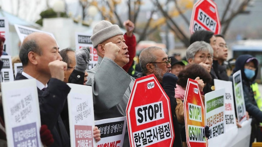 """South Korean members of a civic group shout slogans during a rally to oppose the General Security of Military Information Agreement (GSOMIA) between South Korea and Japan, in front of the government complex where the cabinet meeting is being held, in Seoul, South Korea, Tuesday, Nov. 22, 2016. South Korea's Cabinet on Tuesday approved an intelligence-sharing agreement with Japan to better deal with threats from North Korea, officials said. The signs read """"Stop, the General Security of Military Information Agreement (GSOMIA) between South Korea and Japan."""" (AP Photo/Lee Jin-man)"""