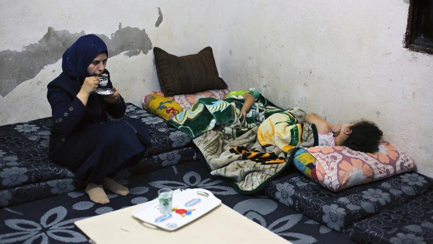 In this Wednesday, Oct. 26, 2016 photo, Syrian refugee Haela Kalawi, 31, whose husband is missing in Syria, drinks coffee as she sits beside her sleeping children at their home in Ouzai, a  poor neighborhood in the Lebanese capital of Beirut. About one-third of 240,000 Syrian refugee households in Lebanon are headed by women, in stark contrast to Syria's traditions which see men as providers and protectors. The husbands of the women surviving on their own are either dead, missing, chose to remain in Syria or tried to make their way to Europe. (AP Photo/Bilal Hussein)
