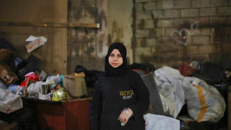 In this Wednesday, Oct. 26, 2016 photo, Syrian refugee Haela Kalawi, 31, poses for a photograph at her workplace, Recycle Beirut, in Ouzai, a poor neighborhood in the Lebanese capital of Beirut. About one-third of 240,000 Syrian refugee households in Lebanon are headed by women, in stark contrast to Syria's traditions which see men as providers and protectors. The husbands of the women surviving on their own are either dead, missing, chose to remain in Syria or tried to make their way to Europe. (AP Photo/Bilal Hussein)