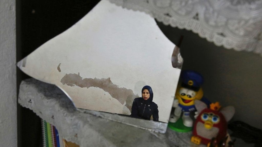 In this Wednesday, Oct. 26, 2016 photo, Syrian refugee Haela Kalawi, 31, is reflected in a mirror as she speaks during an interview with The Associated Press at her home in Ouzai, a poor neighborhood in the Lebanese capital of Beirut. About one-third of 240,000 refugee households in Lebanon are headed by women, in stark contrast to Syria's traditions which see men as providers and protectors. The husbands of the women surviving on their own are either dead, missing, chose to remain in Syria or tried to make their way to Europe. (AP Photo/Bilal Hussein)
