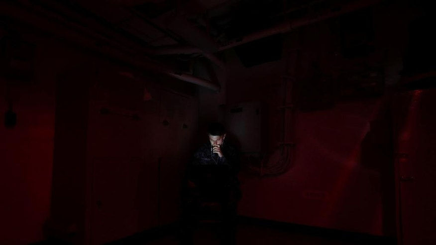 In this picture taken on Monday, Nov. 21, 2016, a U.S. Navy sailor looks at his computer inside the U.S.S. Dwight D. Eisenhower aircraft carrier. The carrier is currently deployed in the Persian Gulf, supporting Operation Inherent Resolve, the military operation against Islamic State extremists in Syria and Iraq. (AP Photo/Petr David Josek)